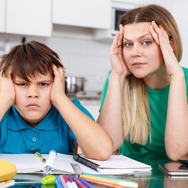 Annoyed mother helping son with homework sitting nearby at kitchen table
